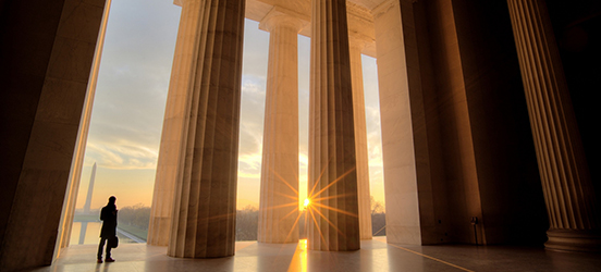 A silhouette of a man standing near the pillars of the entrance of the Lincoln Memorial with the sun setting in the distance, illuminating the Washinton Memorial and the reflecting pool at the National Mall