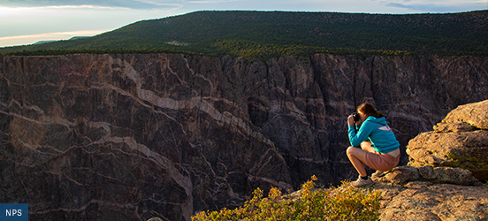 A person squats near the edge of a cliff while taking a picture of Black Canyon of the Gunnison National Park
