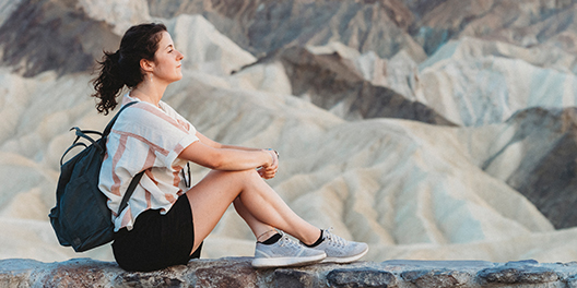 A woman sits on a rock wall and looks out at the unique rock formations of Death Valley National Park