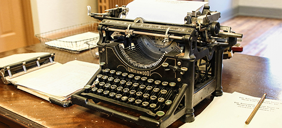 An old typwriter sits on a wooden desk with a blank piece of paper in the carriage, ready for typing