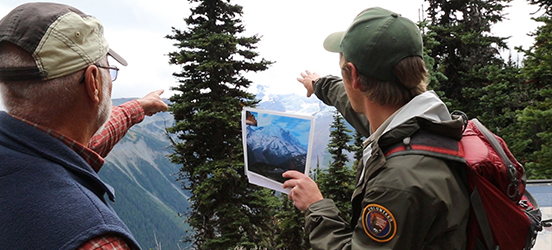 A volunteer and visitor looking and pointing at the mountains at Mount Rainier National Park