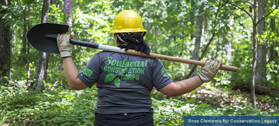 A view of the back of a young adult holding a shovel horizontally, across their shoulders while wearing a hard hat, work gloves, and a Tshirt that says 'Southeast Conservation Corps' while standing in a forested area