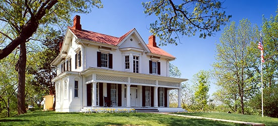 The Frederick Douglass National Historic Site is a white, two story home, with black shutters, a red roof, and a wide open front porch. It's sitting on a little hill with trees around the lush lawn and a flag pole near the porch.