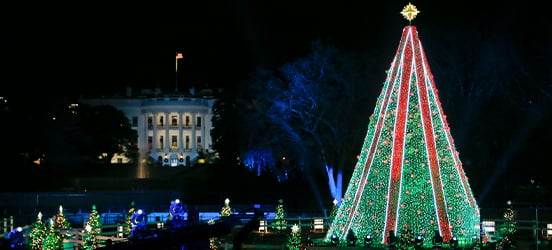 The National Christmas Tree glowing bright during the 2018 lighting ceremony, with the White House gleaming in the background