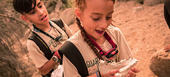 Two children look at a skull fossil replica while on a hike