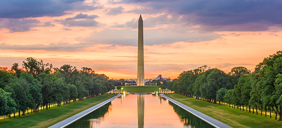 A sunset view of the Washington Monument with the reflecting pool mirroring the monument in the foreground and lights from monuments dotting the National Mall grounds