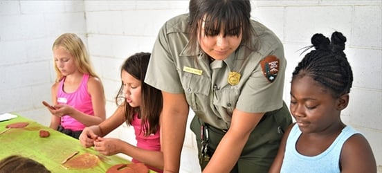 An NPS Ranger helps kids with a clay pottery craft