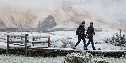 Two people walk the boardwalks in Yellowstone National Park while snow flurries around them