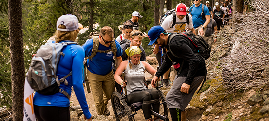 A group of people hiking a dirt path with steep terrain, helping a woman in a wheelchair get over an obstacle on the trail
