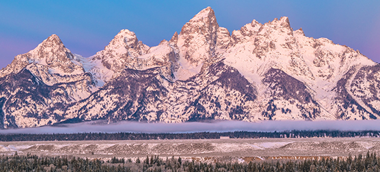 A wide view of the mountains dusted with snow at Grand Teton National Park