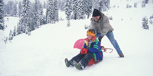 A child sitting on a sled being pushed downhill by a man on the snowy mountains of Lassen Volcanic National Park