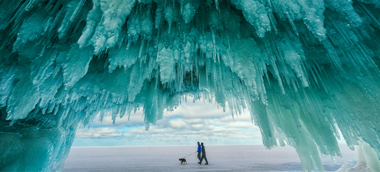 Icicle stalactites cover the roof of a cave at Apostle Islands National Lakeshore and through the cave's opening a coupld can be seen walking their dog on the frozen lake