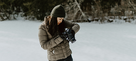 A woman adjusts the settings on her camera while standing in a snowy area with evergreens behind her