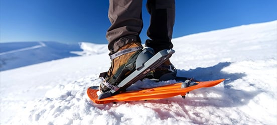A close up of hiking boots halfway clipped into show shoes while the person stands in a snowy covered, mountainous area