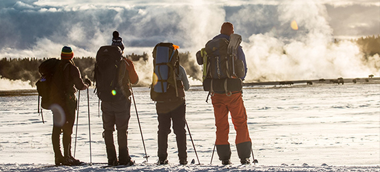 Four hikers, dressed in snow gear, backpacks, cross-country skis, and winter hats, stand together watching steam rise from a hot spring in snow covered Yellowstone National Park