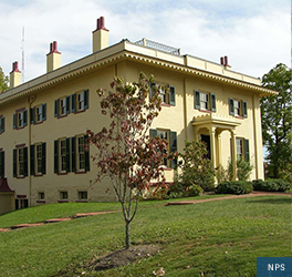 A large yellow home with many windows, each framed with dark shutters, sits on a grassy plot