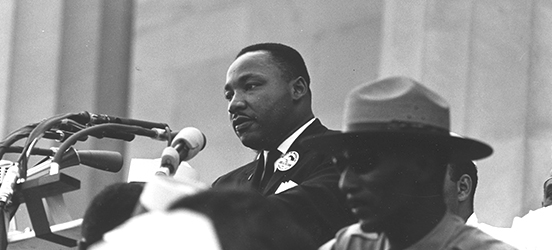 Black and white image of Martin Luther King Jr giving his famous speech at the Lincoln Memorial