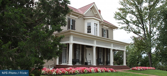 The front of Frederick Douglass's house stands two stories tall with a large, open front porch, edged with bright red and pink flowers.