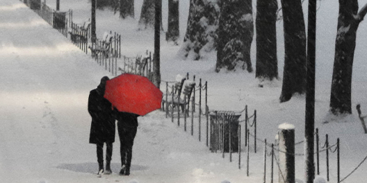 A couple walks together on snow covered sidewalk at the National Mall with a red umbrella on a snowy evening