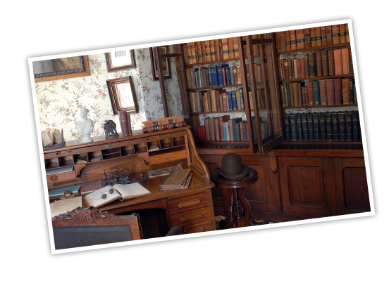 The library at Frederick Douglass National Historic Site, showing a wooden, built-in bookcase filled with books next to an open rolltop covered in more books and ledgers