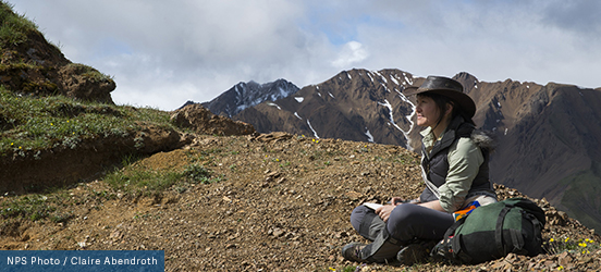 A woman sits near a mountain top ledge with her hiking pack beside her, looking at the scenery of the trail in front of her.