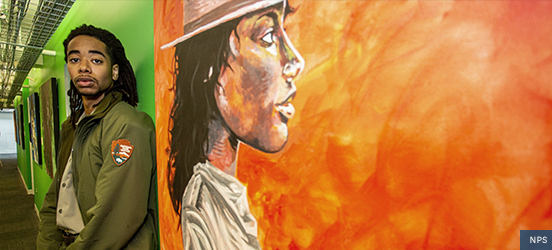 Elijah Prince stands in front of a large canvas painting he did of the profile of a black, female park ranger with an orange and red background