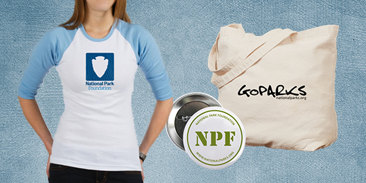 A collage of National Park Foundation merchandise including a baseball style shirt, tote bag, and pin