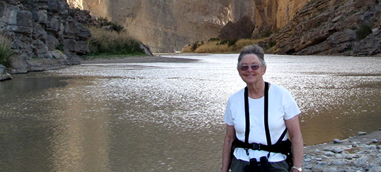 Janean smiles to the camera while standing in the bottom of a canyon with a river of water behind her