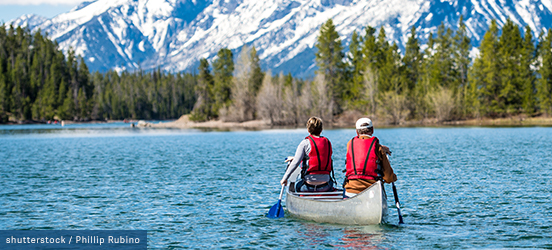 A couple canoes along snake river in Grand Teton National Park