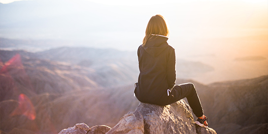 A woman sits on top of a rock, overlooking the mountains in Yosemite National Park