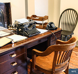 A typewriter sits on top of a large, wooden desk next to papers and a rotary phone