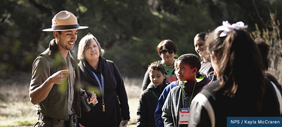 A group of students listen to a park ranger as he talks to them on a trail at Santa Monica Mountains National Recreation Area