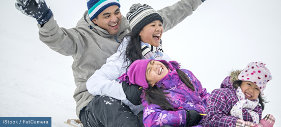 A family of 4 share a toboggan as they sled down a snowy hill