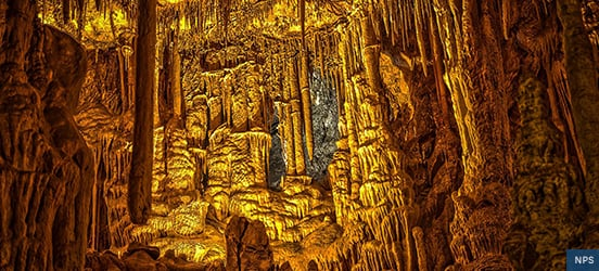 Intricate stalactites cover a cavern wall and are illuminated from a light below