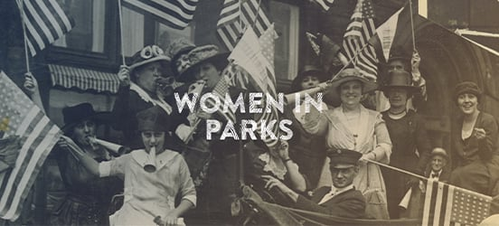 A historic, black and white photo of women dreseed in formal clothes, wearing large hats and standing together while holding American flags and noise makers