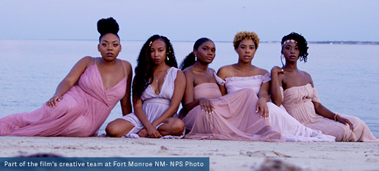 5 African American women wear blush pink, flowing gowns as they sit on the beach at Fort Monroe National Monument