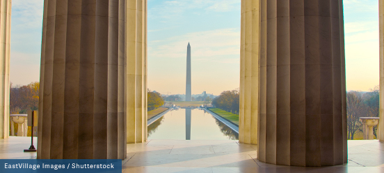 A view of the Washington Monument on a sunny day from insde the Lincoln Memorial, its pillars frame the distant monument