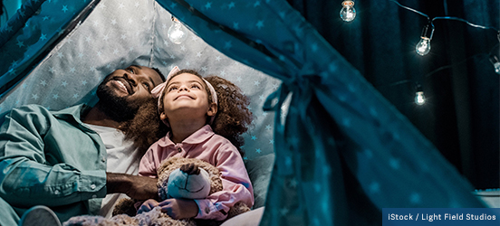 Father and daughter cuddle together in a play tent with twinkle lights strung above it while in their pajamas