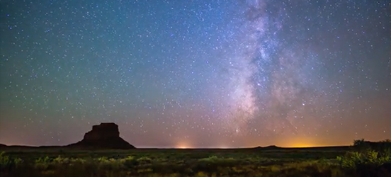 A still from the timelapse showing a colorful, starry sky appearing to move as the night passes over a silhouette of the rock formations at Chaco Culture National Historical Park