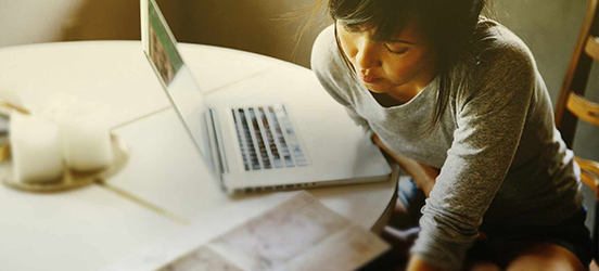 A close-up view of a woman as she sits at a table with her laptop and a map