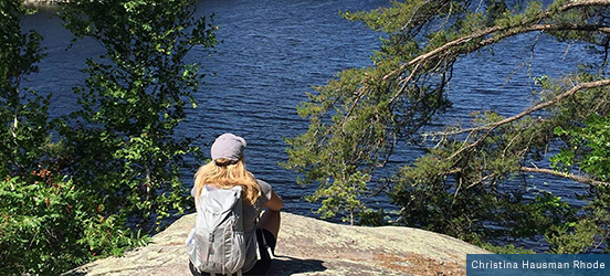Christina Hausman Rhode sits on a large rock on the edge of the water, with trees covering the entire shoreline at Voyageurs National Park