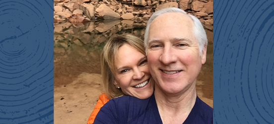 Donor Allie hugs her husband, David, resting her head on his shoulder as they smile for the camera while on a hike on a dirt path in Zion National Park