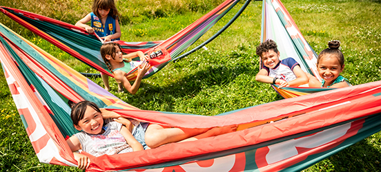 Kids grin at the camera while lounging in brightly colored hammocks, hanging over a green lawn