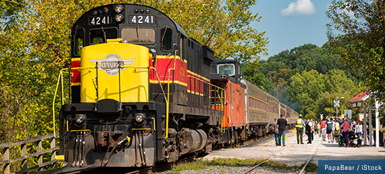 The Cuyahoga Scenic Train sits at a tree-lined station while passengers group up to board
