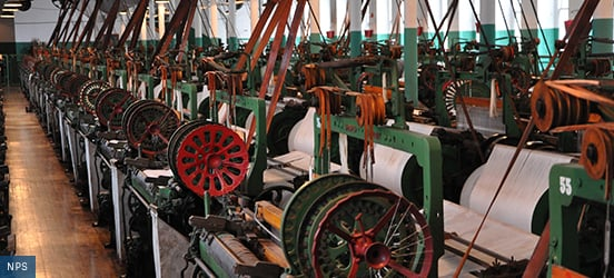Mechanical looms line the Boot Weave Room from wall to wall with only space for a walking aisle down the middle at Lowell National Historical Park