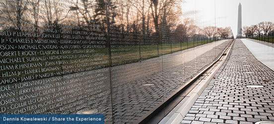 The Vietnam Memorial wall of names reflects the path and trees in the park and the Washington Memorial stands in the distance