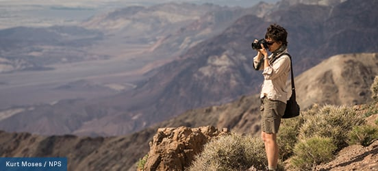 A photographer with camera stands on the side from a mountain overlook, with rocky slopes in the background