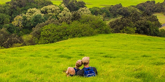 A man and woman sit together on a grass covered hill, overlooking more hills and clusters of trees at Hawaii Volcanoes National Park