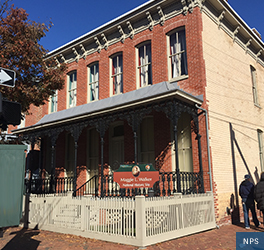 A corner view of the of Maggie L. Walker National Historic Site showing the red brick two story builing's back proch with French style, black iron railings, and a white picket fence at the sidewalk