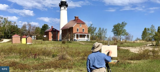 A painter stands at their easel as they paint the lighthouse and brick building in the distance at Picutred Rocks National Lakeshore